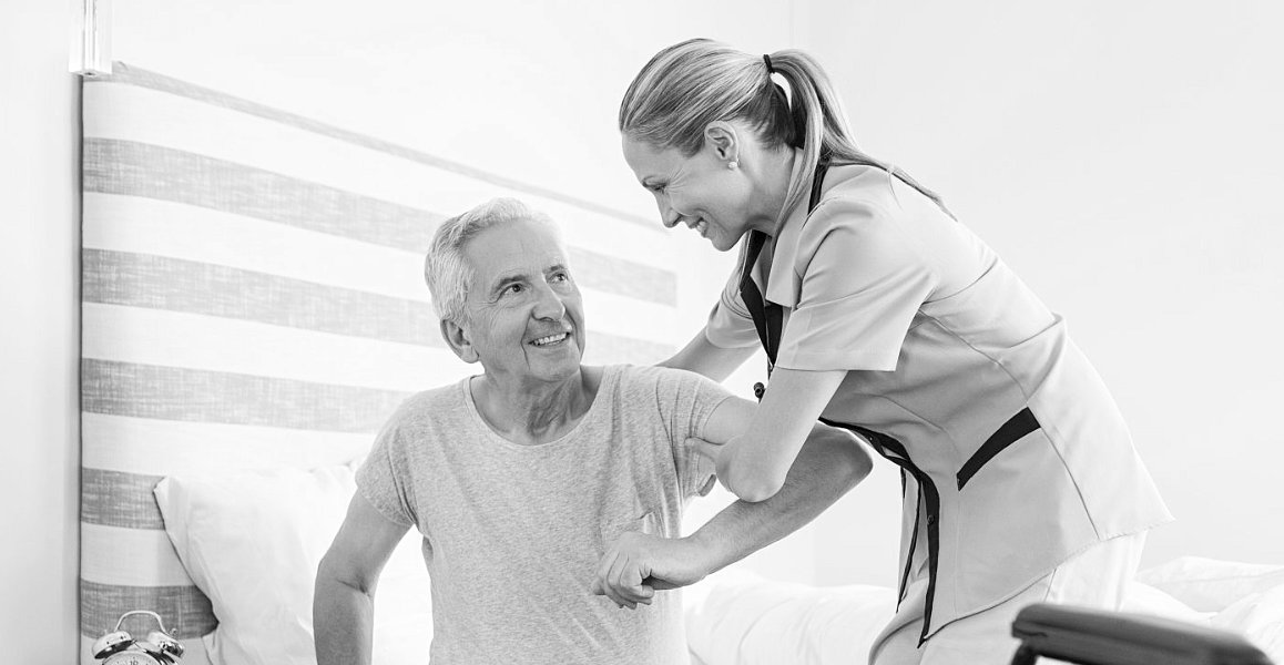 caregiver assisting an elder man