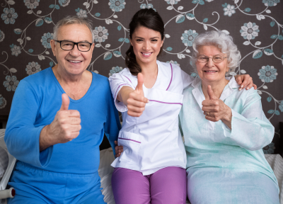 two seniors and a caregiver doing a thumb's up