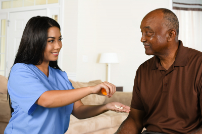 caregiver giving a medicine to a senior man